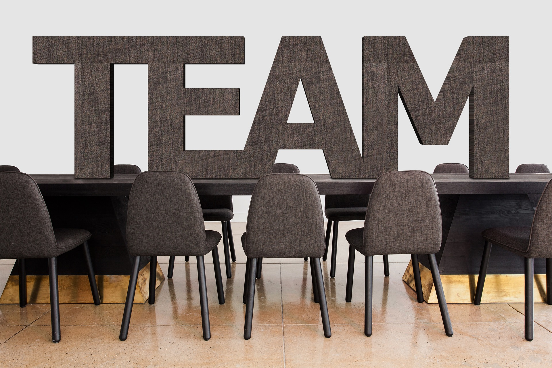"""The word """"Team"""" placed above a conference table"""