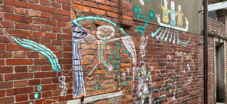 red brick wall with colorful Taiwanese art - with images of nature and folktale characters