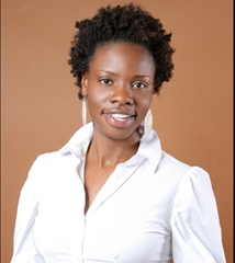image of African American woman with short hair and white button-up blouse. Image background is solid tan